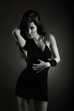 posera kvinnabarn för härlig svart klänning Arkivfoton