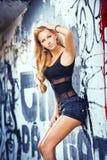 posera mode för blond flicka nära grafittiväggen Royaltyfri Foto