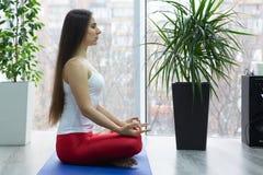 Poserar övande yoga för den unga attraktiva kvinnan som sitter i den Ardha Padmasana övningen, halva Lotus och att utarbeta, den  royaltyfri foto