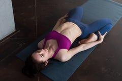 Poserar bärande sportar behån och damasker som för den nätta Caucasian flickan gör sträcka yogaövningen som ligger, i att vila hj Fotografering för Bildbyråer