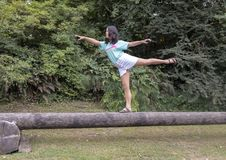Poserar den åriga Amerasian flickan för tretton i en dans på en journal, Washington Park Arboretum, Seattle, Washington royaltyfria foton