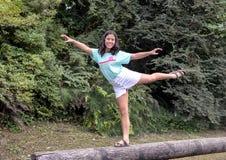 Poserar den åriga Amerasian flickan för tretton i en dans på en journal, Washington Park Arboretum, Seattle, Washington royaltyfri foto