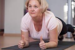 Poserar den övande plankan för den nätta mellersta åldriga kvinnan på idrottshallen royaltyfri bild
