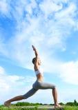 Poserar den övande Yogakrigare för kvinnan. arkivbild