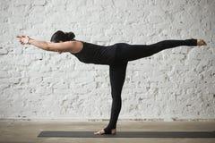 Poserar den attraktiva kvinnan för ung yogi i krigare tre, vindbackgrouen Arkivfoton