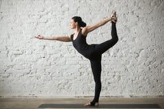Poserar den attraktiva kvinnan för ung yogi i Natarajasana, vit vindbac fotografering för bildbyråer