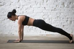 Poserar den attraktiva kvinnan för ung yogi i planka, vit vindbakgrund Fotografering för Bildbyråer