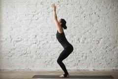 Poserar den attraktiva kvinnan för ung yogi i stol, vit vindbakgrund Arkivfoto