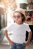 Poserar den bärande vita t-skjortan för den asiatiska flickan mode royaltyfri bild