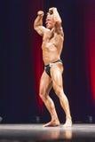 Poserar den dubbla bicepens för kroppsbyggareshower på etapp i mästerskap Arkivbilder