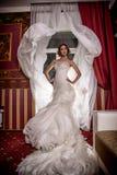 Poserar den härliga bruden för modemodefotoet med lockigt hår i en ursnygg bröllopsklänning med dyrbart perfekt i fantastisk inre arkivfoton