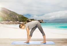 Poserar den intensiva elasticiteten för kvinnadanandeyoga på stranden Royaltyfria Bilder