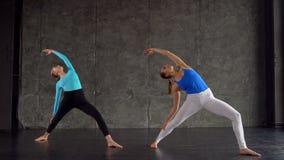 Poserar den mång- ras- gruppen för yogagrupp av kvinnor som övar sund livsstil i krigare för konditionstudioyoga stock video