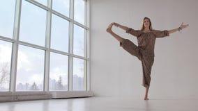 Poserar den praktiserande fördjupade hand-till-stor-tån för den spensliga yogakvinnan lager videofilmer