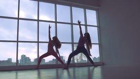 Poserar den praktiserande fördjupade triangeln för två spensliga yogakvinnor i studion med naturligt ljus arkivfilmer