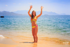 poserar den slanka flickan för blondinen i bikini händer uppe i luften på stranden Arkivfoton