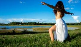 Poserar den spanska kvinnan för den unga brunetten som gör yoga för krigare 2, i ett fält bredvid en sjö med långt lockigt hår royaltyfria foton