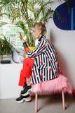 Poserar det ikl?dda stilfulla randiga omslaget f?r modeung flickabloggeren och den r?da byxan att sitta p? stolen med rosa p?ls arkivbilder