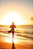 Poserar det praktiserande trädet för yogakonditionkvinnan på stranden på solnedgången Royaltyfri Foto
