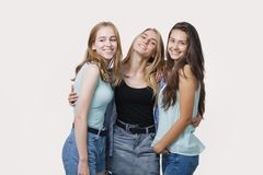 Poserar iklädd tillfällig stil för tre lyckliga flickor i studion royaltyfri bild