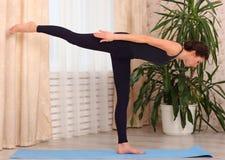 Poserar praktiserande yoga för den unga attraktiva kvinnan som står i krigare tre, hemma Royaltyfri Bild