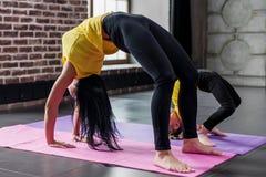 Poserar praktiserande yoga för kvinna- och barnflicka tillsammans hemma och att stå i bro royaltyfri fotografi