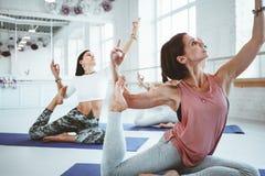 Poserar utbildande yoga för stark färdig kvinna på kondition som är matt samman med grupp människor på bakgrund Healthe omsorg oc arkivfoton