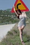 Poserar varm kläder för kvinnakläder framdelen av en vänd för fara för trafiktecken Arkivfoto