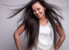 Poses asiáticas agradáveis novas da menina no estúdio. Fotos de Stock