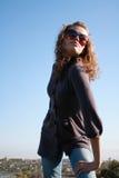 Poses da menina de encontro ao céu azul Imagem de Stock Royalty Free