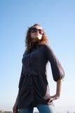 Poses de fille contre le ciel bleu Photo stock