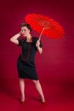 Poses de pin-up de fille avec le parapluie rouge Photos stock