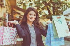 Poses de sorriso da mulher à câmera com sacos de compras Imagens de Stock Royalty Free