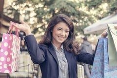 Poses de sourire de femme à l'appareil-photo après l'achat Image libre de droits