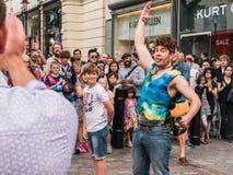 Poses do executor da rua com voluntários da audiência, perto do peixe-agulha de Covent Fotografia de Stock