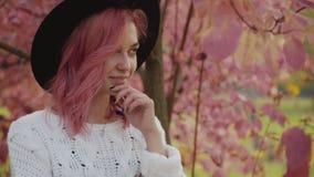 Poses faciles de fille mystérieuse à l'arbre rose avec le sourire sur le visage banque de vidéos