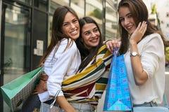 Poses felizes das jovens mulheres à câmera com sacos de compras Imagens de Stock Royalty Free