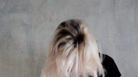 Poses louras da mulher elegante com cabelo em um fundo cinzento filme