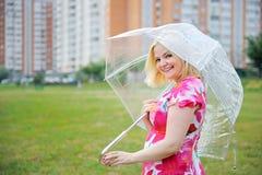 Poses louros adoráveis da mulher ao ar livre com guarda-chuva Imagem de Stock