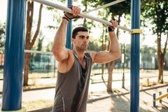 Poses masculines d'athlète sur la barre horizontale extérieure photographie stock