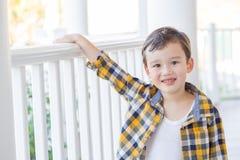 Poses novas adoráveis do menino da raça misturada em seu Front Porch foto de stock