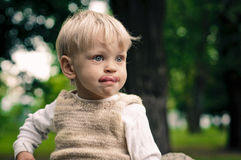 Poseur. Little boy shows his tongue in reverie Royalty Free Stock Photos