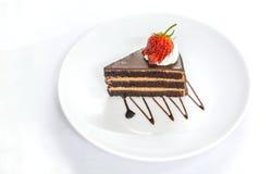 Posez le gâteau de chocolat foncé garnissant avec la fraise rouge coupée en tranches Images libres de droits