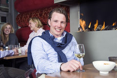 Posh Dandy. A posh looking man with his sweater around his neck and a glass of white wine in his hand sitting at a restaurant table in front of the fireplace Royalty Free Stock Photo
