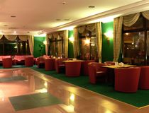 Posh hotel lounge. A picture of a posh hotel lounge with red chairs and green carpet. The tiled portion of the floor reflects the light form the lamps on the Royalty Free Stock Images