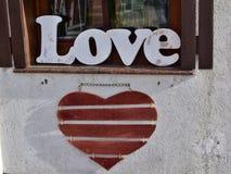 Posição de madeira 'do amor 'da palavra na soleira e no coração de madeira vermelho que penduram na parede na rua da cidade fotografia de stock