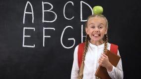 Posição adorável da estudante com a maçã na cabeça, tendo a boa ideia, criança esperta filme