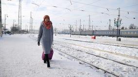 Posição adulta da menina com a mala de viagem roxa da bagagem na estação de trem durante o tempo de inverno vídeos de arquivo