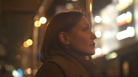 Posição adulta da senhora no transporte da parada do ônibus e na iluminação de espera da apreciação filme
