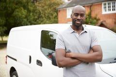 Posição adulta preta nova do comerciante ao lado de sua camionete branca, perto acima, fim acima fotografia de stock